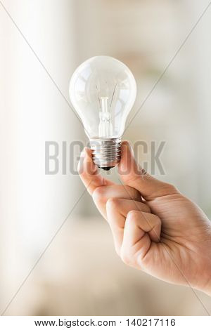 recycling, electricity, idea, environment and ecology concept - close up of hand holding lightbulb or incandescent lamp