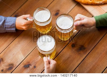people, leisure and drinks concept - close up of male hands with beer mugs at bar or pub
