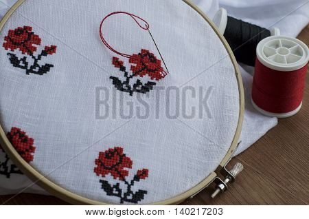 Hand embroidery cross-stitch flower ornament on a white fabric in the wooden embroidery frame red and black thread