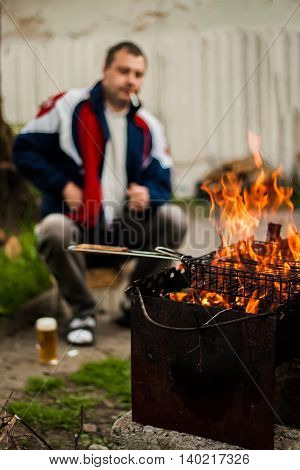 Man Drinks Beer, Smokes And Looks At The Fire