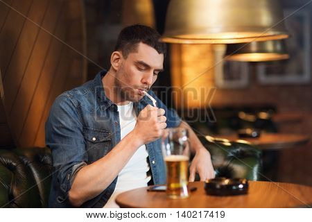 people and bad habits concept - man drinking beer and smoking cigarette at bar or pub