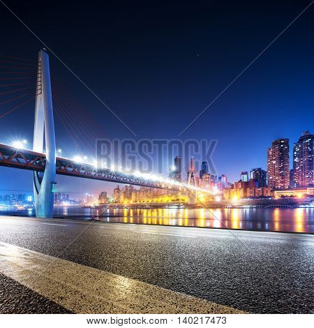 cityscape and skyline of downtown near bridge of chongqing at night from empty road