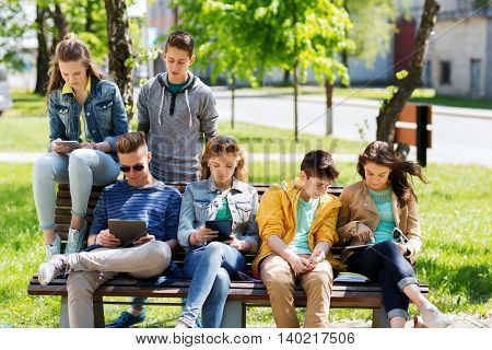 education, high school and people concept - group of happy teenage students with with tablet pc computers at campus yard