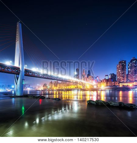 cityscape and skyline of downtown near bridge of chongqing at night