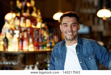 people and leisure concept - happy smiling young man at bar or pub