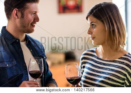 Happy young couple talking while having wine at restaurant