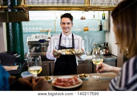Portrait of young bartender serving food to customers at counter in restaurant
