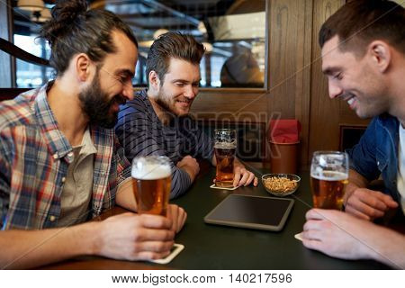 people, men, leisure, friendship and technology concept - happy male friends with tablet pc computer drinking draft beer at bar or pub