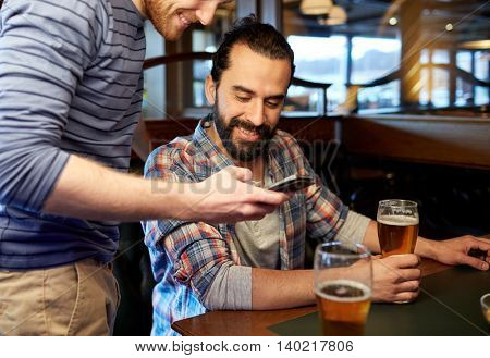 people, men, leisure, friendship and communication concept - happy male friends with smartphones drinking draft beer at bar or pub
