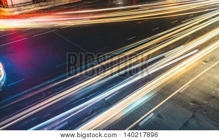 Colorful long exposure light trails across road junction traffic concept or speed abstract