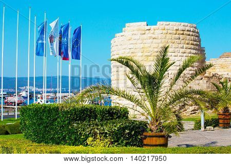 Nessebar, Bulgaria - July 25, 2016: Stone wall and flags at the entrance of old town Nessebar or Nesebar in Bulgaria, Black sea