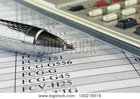 Financial background with calculator table and pen.