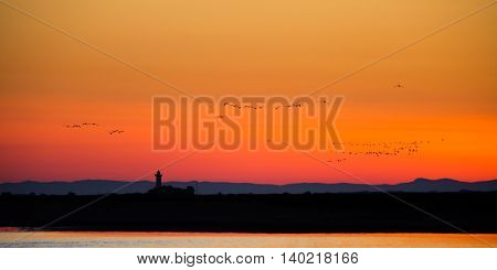 Old lighthouse silhouette in beautiful sunset light, France, Europe