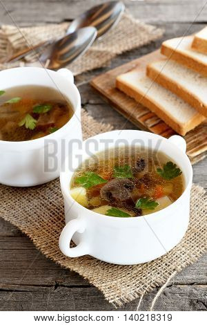 Soup with mushrooms, carrots, potatoes and green parsley. Soup cooked in mushroom broth. Bread slices, spoons, burlap on old wood table. Delicious and healthy dinner and lunch recipe