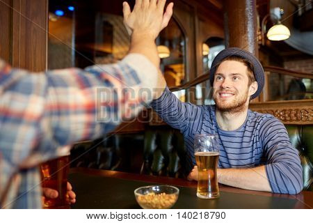 people, men, leisure, friendship and gesture concept - happy male friends drinking draft beer and making high five at bar or pub
