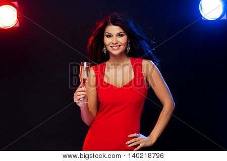 people, holidays, party, night lifestyle and leisure concept - beautiful sexy woman in red dress with champagne glass at night club