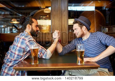 people, leisure, friendship and party concept - happy male friends drinking draft beer and arm wrestling at bar or pub and