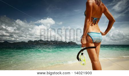 Young woman with wet skin and with a mask standing on sand and going to snorkeling in clear sea