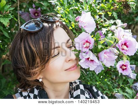 Young caucasian woman sniffs pink flowers in the park. Female portrait. Beauty fashion and nature.