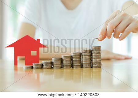 woman put coins to stack of coins and red house blackground