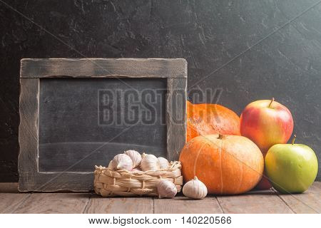 Assortment of farm autumn fruits and vegetables on a rustic wooden table alongside chalk board with blank copyspace for a menu or recipe