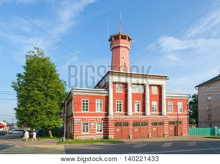 UGLICH RUSSIA - JULY 19 2016: Unknown people walk down street near building of fire department with watchtower. Building was built in years 1809-1811 on standard project. Project author Luigi Rusca