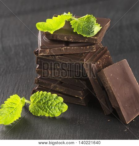 Pieces of dark chocolate and mint on a dark background