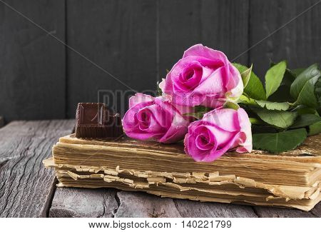 Old Book Pink Roses And Chocolate On A Dark Wooden Background