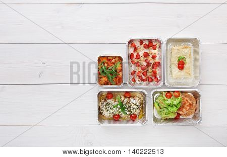 Healthy food restaurant delivery, daily meals and snacks. Diet nutrition, vegetables, meat and fruits in foil boxes. Top view, flat lay at white wood with copy space