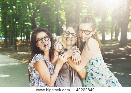 Three beautiful young boho chic stylish girls portrait in park. Happy smiling friends in eyeglasses, having fun outdoors. Attractive young women in summer city, youth fashion