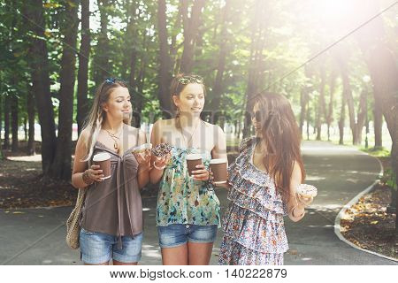 Three beautiful young boho chic stylish girls walking in park. Happy girlfriends talking, female friends having fun outdoors. Attractive young women drink coffee in summer city, youth fashion