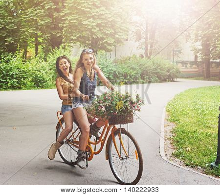 Happy boho chic stylish girls ride together having fun. Beautiful women on bicycles with basket full of wild flower. Female friends, youth and happiness, active summer leisure in park concept.
