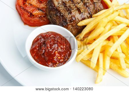 Restaurant food - beef grilled steak with french fries on white plate. Closeup of roasted meat and chips with grilled tomatoes and bowl of barbecue sauce