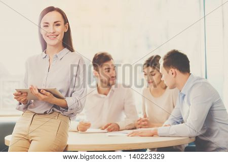 Being successful. Smiling and happy business woman standing in foreground with a tablet in her hands, her co-workers discussing business matters in the background