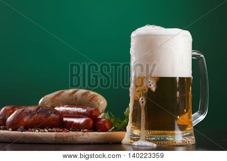 Traditional Oktoberfest menu. Beer in glass with foam snacks sausages grilled. On a green background with free space