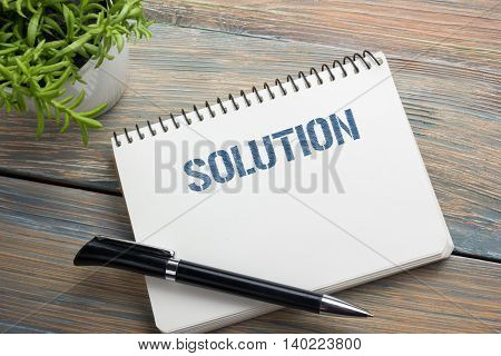 Solution. Notepad with message, pen and flower. Office supplies on desk table top view.