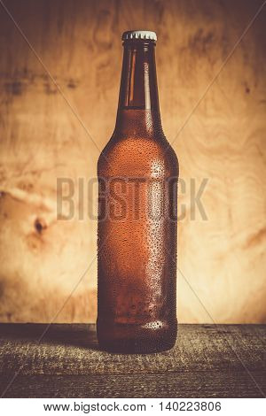 Beer in bottle with ice drops, rustic background , toned