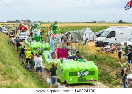 QuievyFrance - July 07 2015: Teisseire Caravan during the passing of the Publicity Caravan on a cobblestoned road in the stage 4 of Le Tour de France on July 7 2015 in Quievy France. Teisseire produces fruit juices and syrups for the food service industry