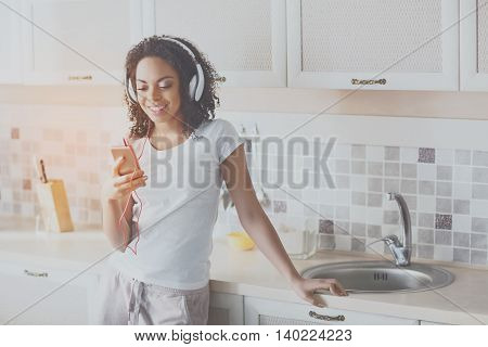 Favorite one. Happy and content young woman enjoying her music at home standing in the kitchen and holding her phone with a smile of bliss