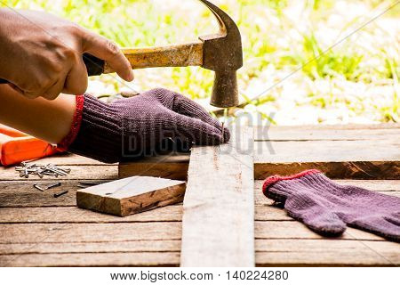 Background Craftsman tool with old hammer with tape measure and small nails and working outdoor view.Background for carpenter and repair and craft country style.