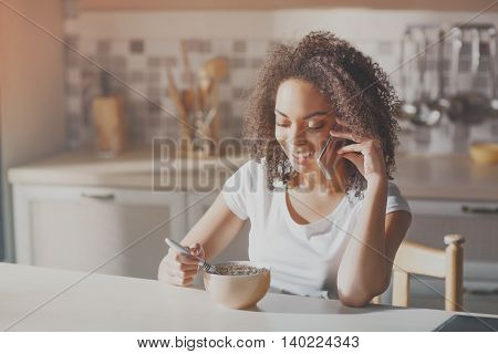 Perfect morning. Happy and positive teen girl eating breakfast in kitchen while talking on her smart phone