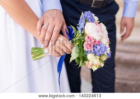 Young married couple holding hands wedding day ceremony