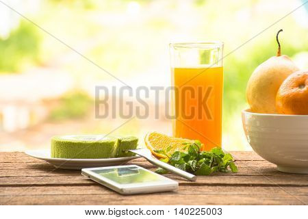 Background fruit in bowl and juice with green tea cake and mint with smartphone.On wooden background outdoor view and holiday with relax .