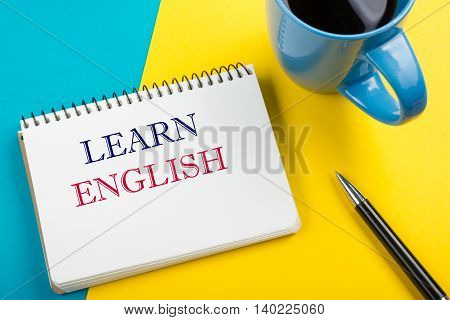 Learn English Text written on notebook page, red pencil and coffee cup. Office desk table top view.