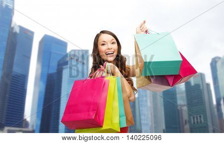 people, holidays, tourism, travel and sale concept - young happy woman with shopping bags over singapore city skyscrapers background