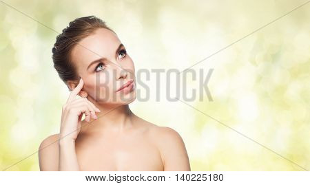 beauty, people and health concept - beautiful young woman touching her face over yellow holidays lights background