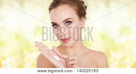 beauty, people, skincare and cosmetics concept - happy young woman with moisturizing cream on hand over yellow holidays lights background