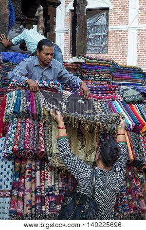 Kathmandu, Nepal - October 19, 2014: A seller showing scarfs to a customer on the market in Kathmandu, Nepal