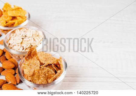 assortment breakfast cereals in small glass dishes on wooden table, almond nuts close up