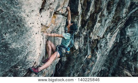 Young woman in safety harness with outfit climbing the rock wall outdoor